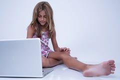 Flicka som använder en bärbar dator med bekymrat uttryck fotografering för bildbyråer