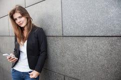 Flicka som använder hennes smartphone Arkivfoto