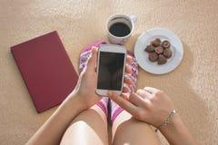 Flicka som använder hennes telefon i säng Arkivbild