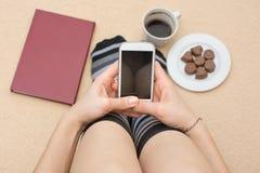 Flicka som använder hennes telefon i säng Royaltyfri Foto