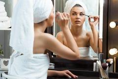Flicka som använder mascara royaltyfri fotografi