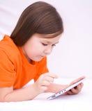 Flicka som använder minnestavlan Fotografering för Bildbyråer