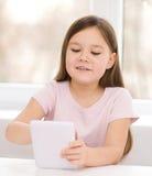 Flicka som använder minnestavlan Arkivbilder