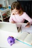 Flicka som använder mobiltelefonen, i stället för att studera i sovrum Royaltyfria Bilder