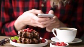 Flicka som använder mobiltelefonen under frukosten i kafé arkivfilmer