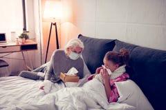 Flicka som använder servetter, medan ha den rinnande näsan nära hennes att bry sig farmor arkivfoto