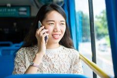 Flicka som använder telefonen på den offentliga bussen Arkivbild