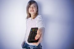 Flicka som använder TV- eller videofjärrkontrollen och skjuter makten arkivbild