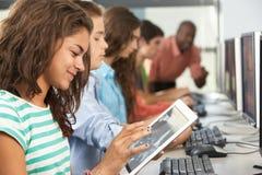 Flicka som använder den Digital minnestavlan i datorgrupp Arkivbild