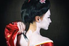 Flicka som applicerar geishamakeup Arkivfoton