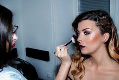 Flicka som applicerar makeup med borsten på framsida av skönhetflickan i studion arkivfoton