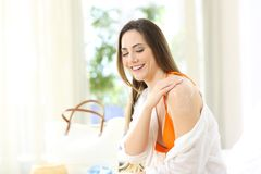 Flicka som applicerar sunscreen på skuldror i ett hotellrum royaltyfri foto