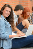 Flicka som arbetar på bärbar datorvänner i bakgrund Arkivfoto