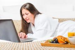 Flicka som arbetar på en dator i säng Fotografering för Bildbyråer