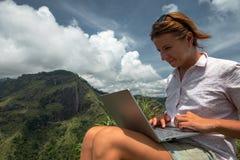 Flicka som arbetar på hennes dator på överkanten av berget royaltyfri bild