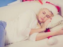 Flicka som bär den santa hatten som hemma sover på soffan Arkivbild