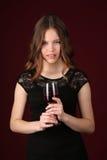 Flicka som bär den svarta klänningen med vin close upp mörkröd bakgrund Fotografering för Bildbyråer
