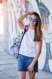 Flicka som bär den tomma vita t-skjortan, jeans som poserar mot den grova gataväggen Royaltyfri Bild