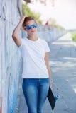 Flicka som bär den tomma vita t-skjortan, jeans som poserar mot den grova gataväggen Arkivfoto