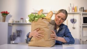 Flicka som bär den tunga packen av livsmedel, problem med leveransen, offline-shopping arkivfilmer