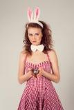 Flicka som bär dräkten för easter kanin med ägg i korg Arkivbild