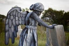 Flicka som bär en ängeldräkt i en gammal allvarlig gård royaltyfria foton