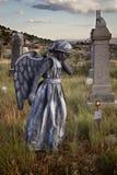 Flicka som bär en ängeldräkt i en gammal allvarlig gård fotografering för bildbyråer