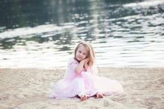 Flicka som bär en lång bohemisk klänning som sitter på stranden på en semesterhelg En ensam dam sitter på stranden bara Lopp och  arkivfoton