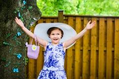 Flicka som bär en stor solhatt med händer upp Royaltyfri Foto