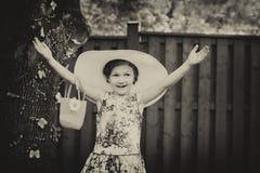 Flicka som bär en stor solhatt med tappning för händer upp - Fotografering för Bildbyråer