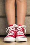 Flicka som bär ett par av röda gymnastikskor arkivfoton