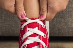 Flicka som bär ett par av röda gymnastikskor royaltyfri bild