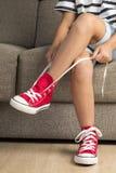 Flicka som bär ett par av röda gymnastikskor arkivbilder