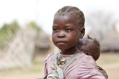 Flicka som bär hennes syster i södra Sudan Arkivfoton