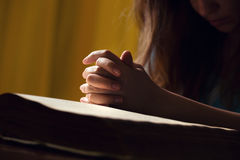 Flicka som ber med händer på bibeln Arkivfoto
