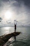 Flicka som ber på solen vid havet Royaltyfria Bilder