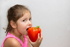 Flicka som biter in i en peppar Arkivbild