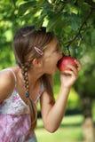 Flicka som biter in i ett äpple arkivfoto