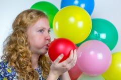 Flicka som blåser blåsa upp den färgade ballongen arkivbilder
