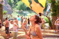 Flicka som blåser bubles på Ozora Festiva Arkivbilder
