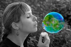 Flicka som blåser en såpbubbla i formen av en planet stj?rnor f?r planet f?r bakgrundsjord fulla Jord pengar f?r huset f?r homeow arkivbild