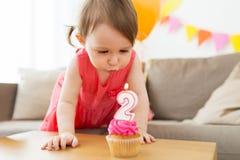 Flicka som blåser för att undersöka på muffin på födelsedagen royaltyfri foto
