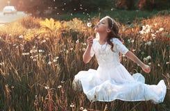 Flicka som blåser frö från en blommamaskros i hösten arkivfoton