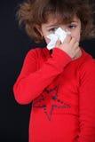 Flicka som blåser hennes näsa Arkivfoton