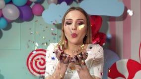 Flicka som blåser på konfettier på ljus bakgrund
