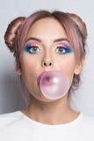 Flicka som blåser stor bubbelgum Arkivbild