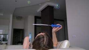 Flicka som blåser upp såpbubblor lager videofilmer