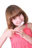 Flicka som borstar hennes tänder med en tandborste arkivfoto