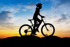 Flicka som cyklar på bergskymningtid Arkivbild