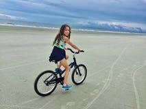 Flicka som cyklar på stranden Fotografering för Bildbyråer